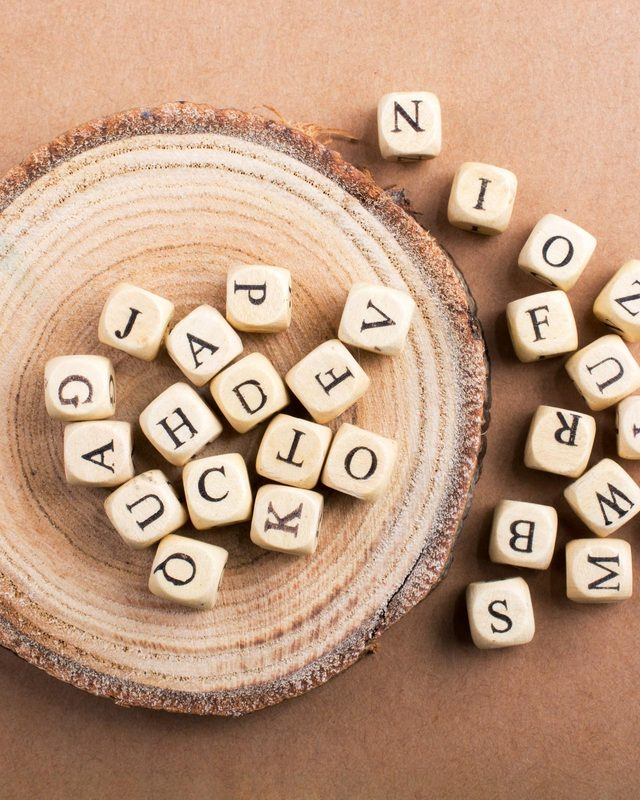 letter tiles on wood slide; brown paper background