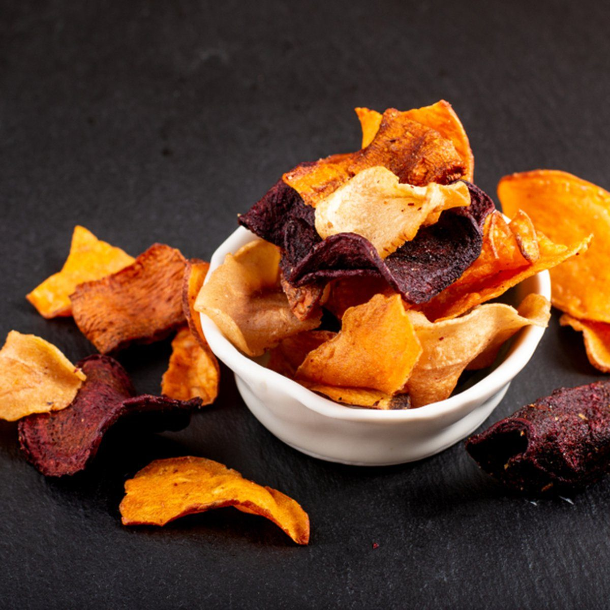 Food concept assortment of vegetable chips on black slate plate