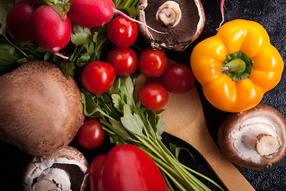 Close up image of different delicious fresh and healthy vegetables on dark background in studio photo
