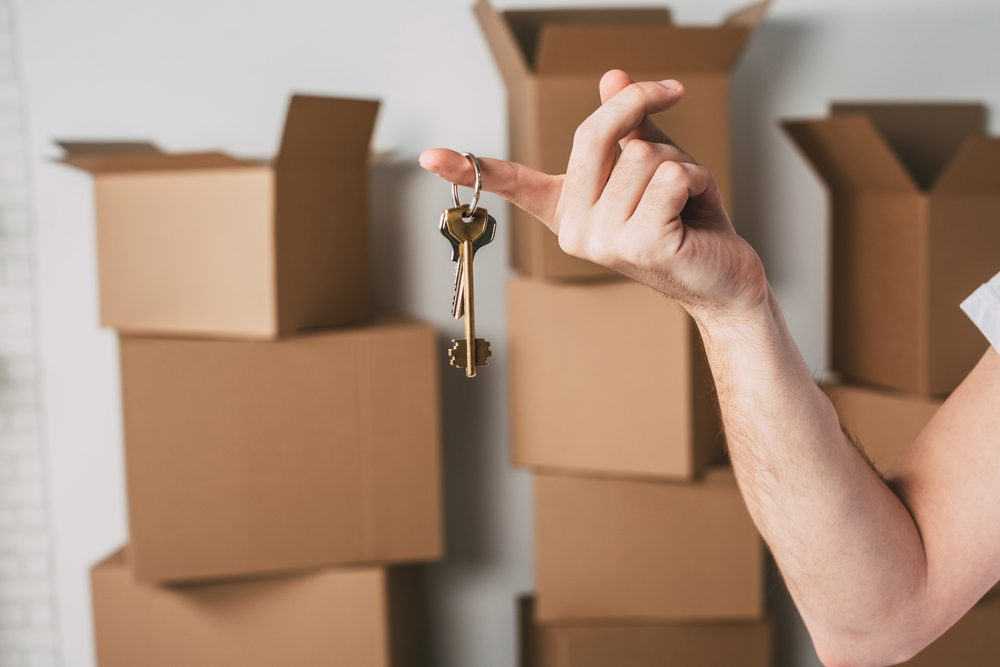 New house. Key to a new apartment on boxes background.