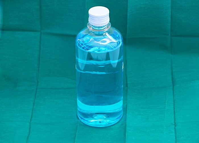 blue ethyl alcohol liquid in plastic transparent bottle on green surgery background
