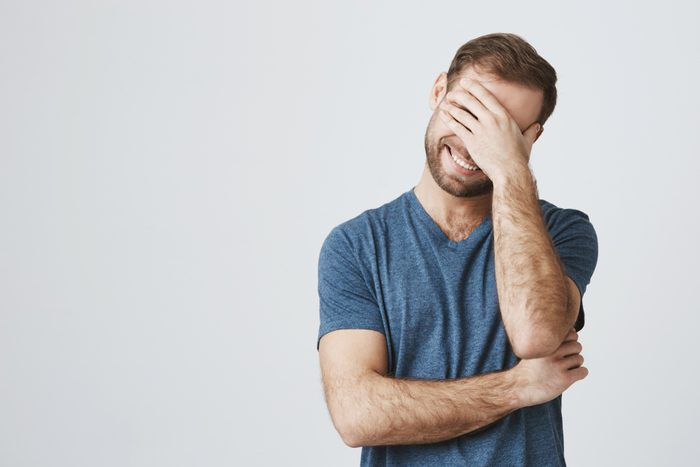 Cheerful caucasian male with stubble keeps hand on head, laughs as has fun with friends, isolated against gray background. Happy smiling guy has happy expression, hears pleasant news