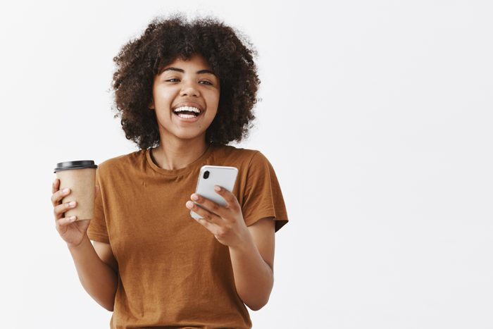 Waist-up shot of trendy carefree african american girl with curly hair in brown t-shirt laughing while talking with friends drinking coffee from paper cup and holding smartphone over gray background