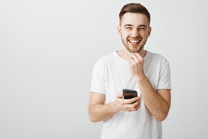 Guy reading joke from internet laughing out loud spending time amused and entertained smiling broadly at camera touching beard and squinting from joy holding smartphone playing in great game on phone