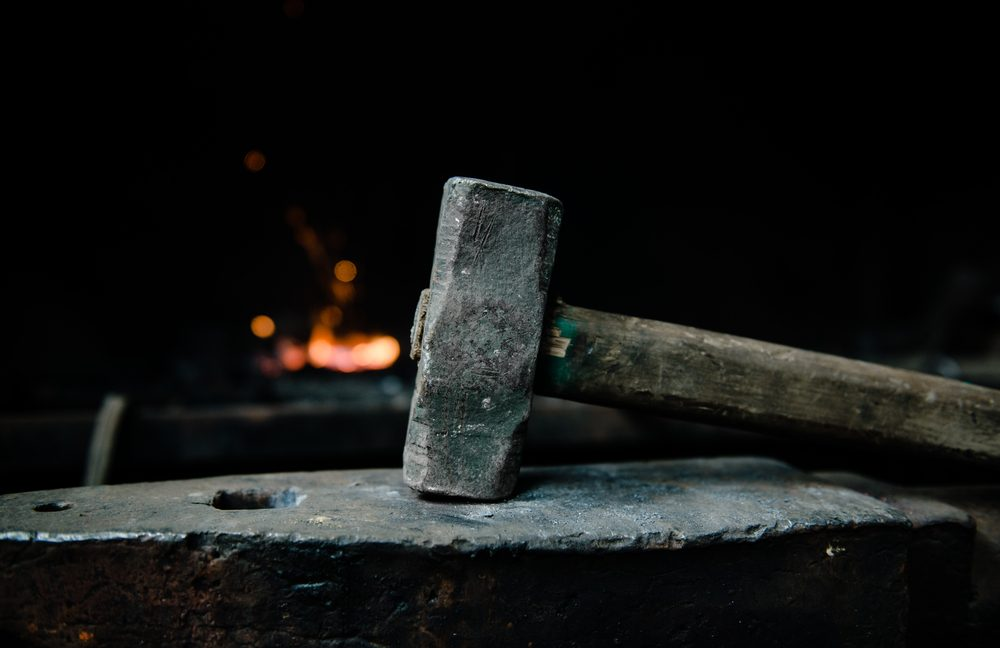 blacksmith hammer on the anvil against the background of fire