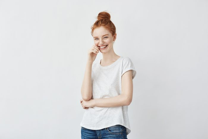 Portrait of young stylish freckled girl laughing with hand on cheek looking at camera. Copy space. Isolated on white