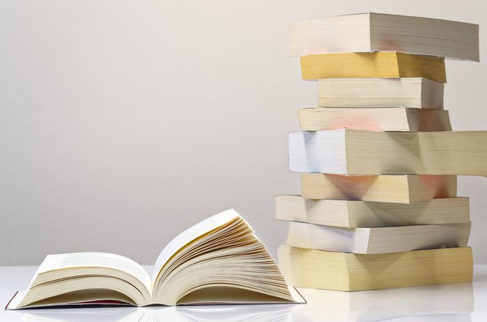 Open book and pile of books on the white table with light grey background