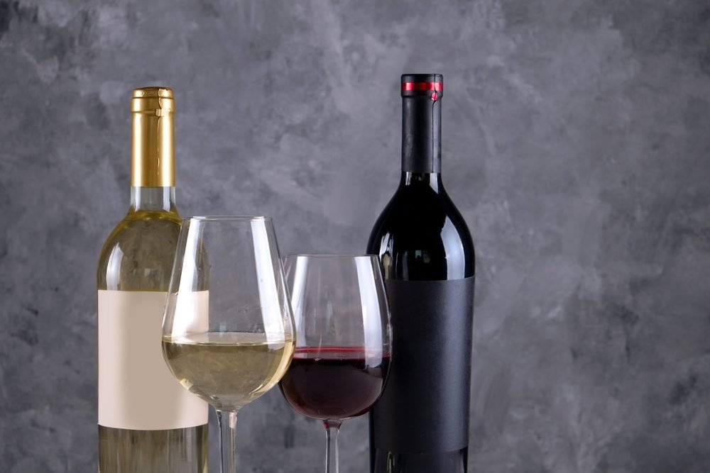 Two bottles of red and white wine with matte black & white blank labels on concrete wall background. Wineglasses half full with vintage expensive wine of different type. Close up, copy space.