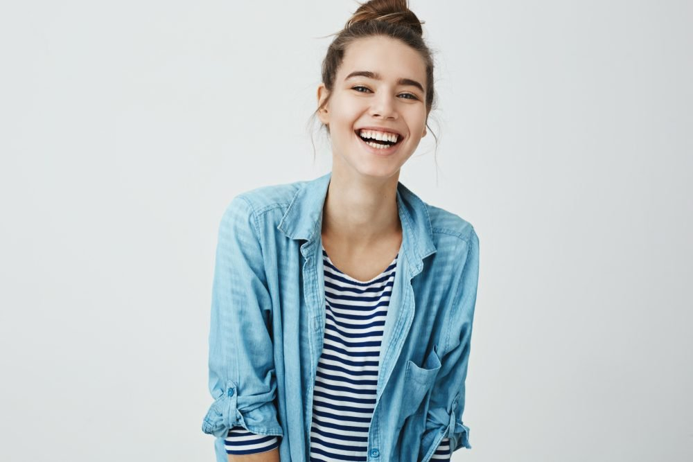 Girl likes funny jokes. Smart good-looking student with bun hairstyle trembling from laugh, smiling positively and being in great mood while standing over gray background. Woman watch hilarious show