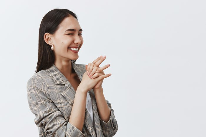 Studio shot of good-looking joyful woman laughing from joy and enthusiasm, standing half-turned over gray background, clasping hands together, looking right, cheering on b-day party