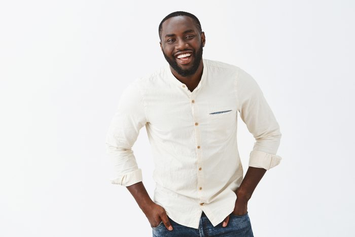 Charming funny African American mature male trying make jokes, impress cute woman, chuckling and smiling broadly, tilting towards camera, holding hands in pockets, being little shy over grey wall