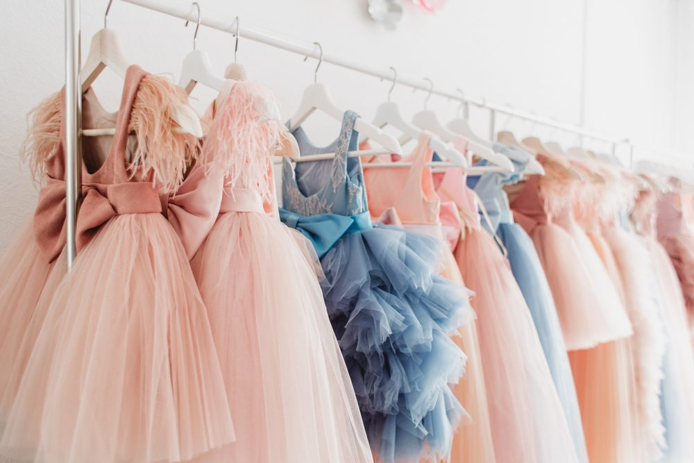 b319f2fcd1 Donate old formal attire to  Operation Prom. Beautiful dressy lush pink and  blue dresses for girls on hangers at the background of white