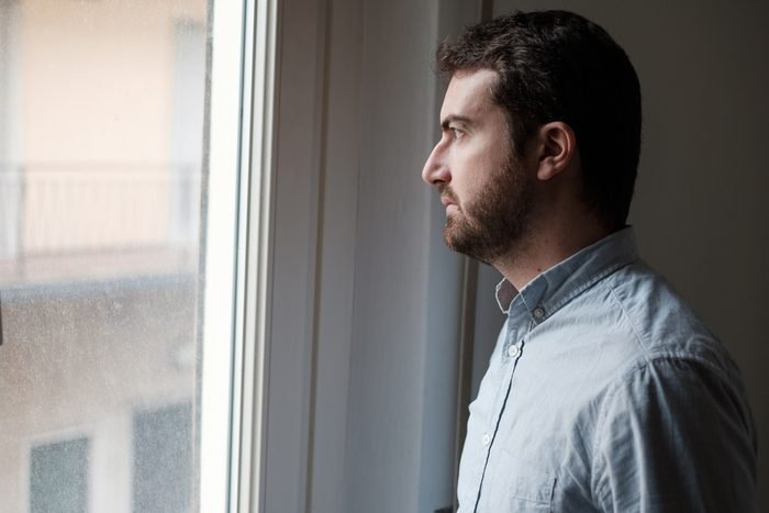 Portrait of sad man looking out of the window