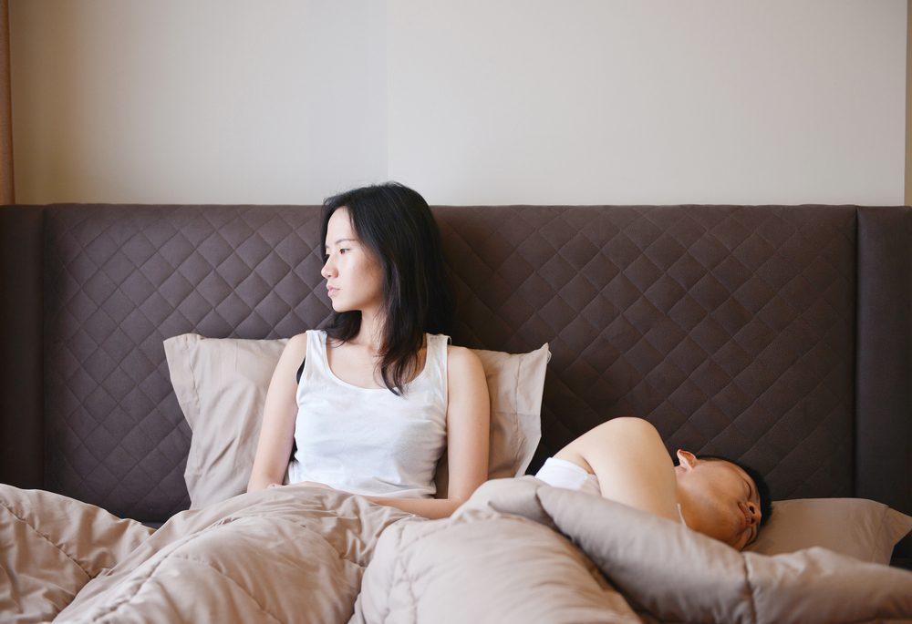 sad depressed woman thinking on bed , boring of her husband in luxury bedroom