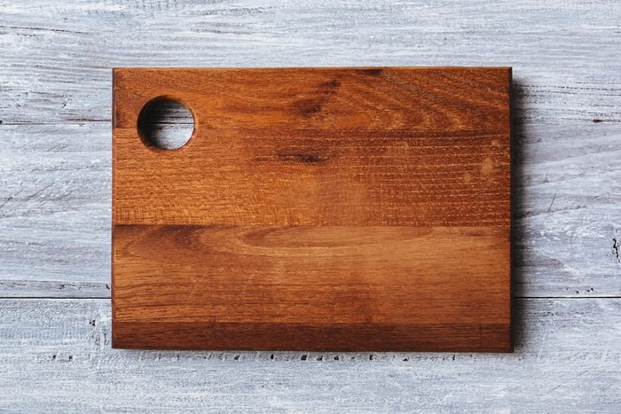 Cutting board on the wooden background. Toned photo.