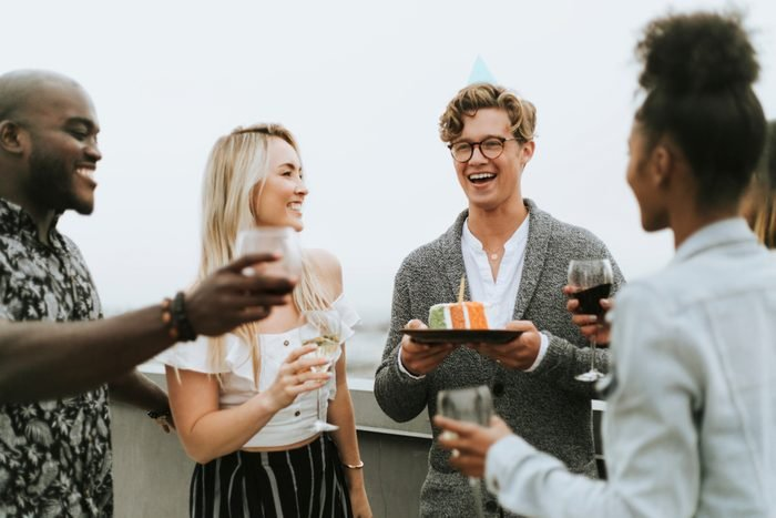 Cheerful friends celebrating at a rooftop birthday party
