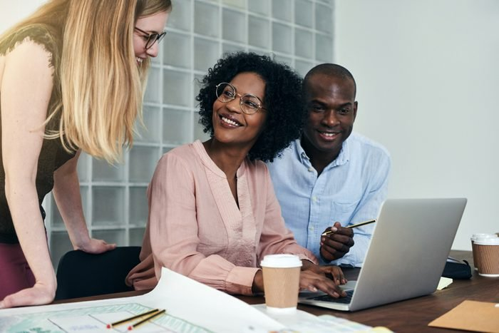 Diverse group of colleagues smiling and having a discussion over a laptop while working together at a desk in a modern office