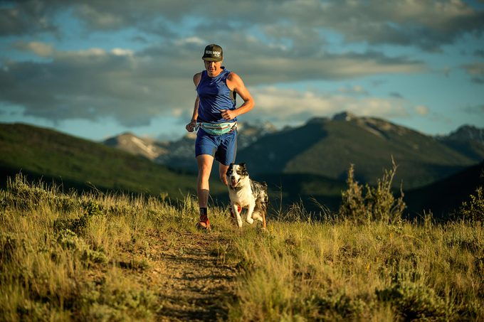 Man and dog running together in mountains, Experts say that humans need to help dogs understand their limits in tough terrain.