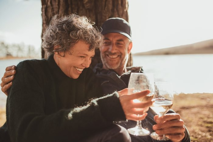 Portrait of relaxed mature couple having a glass of wine at campsite. Senior man and woman toasting wine at on summer day.
