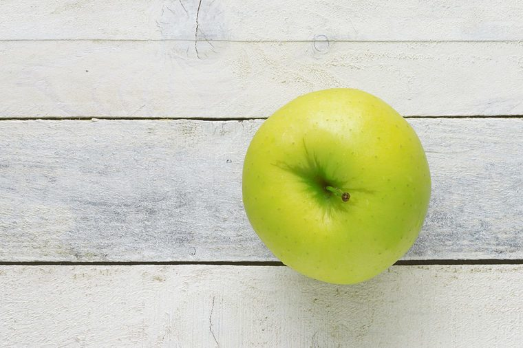 A green apple on a white wooden table. Top view. Empty copy space for editor's text.