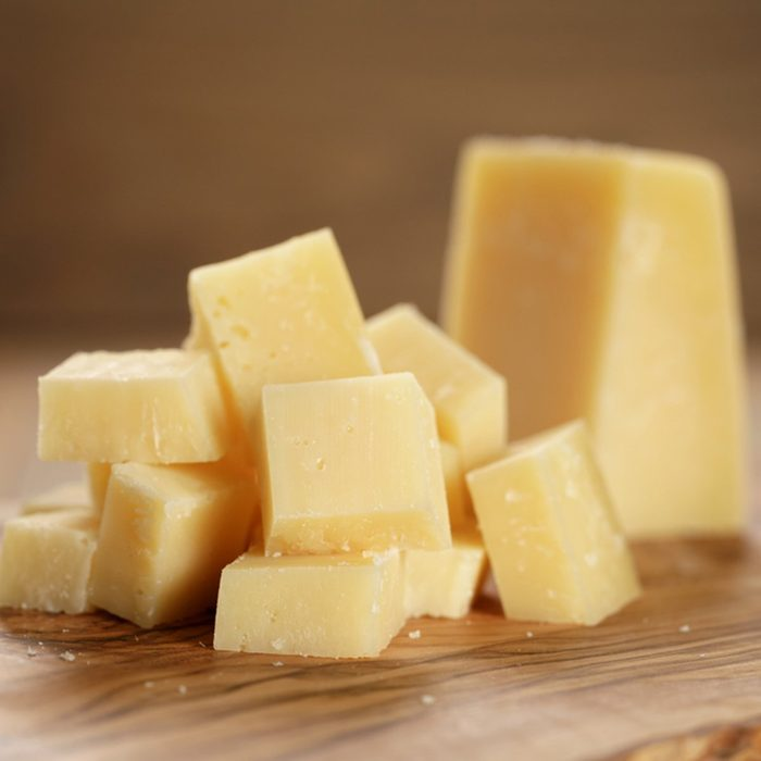 parmesan cubes on olive wooden board, shallow focus