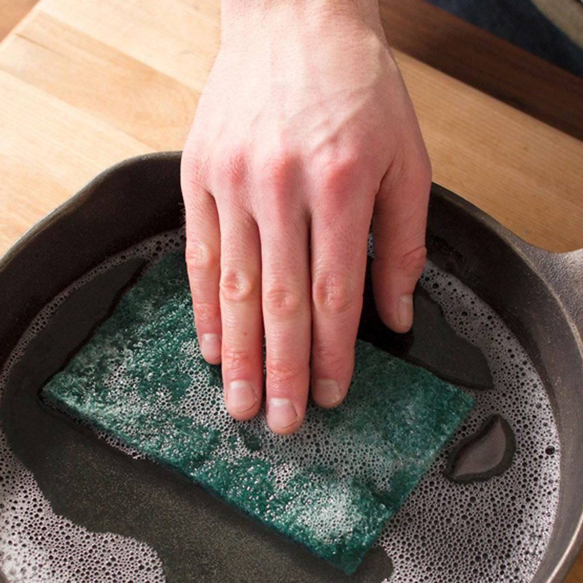 Hand pushing a sponge into a water-filled skillet