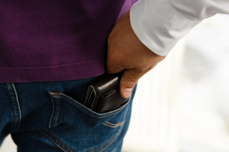 Close-up of a man's hand stretches to the pocket in which sticks out a black wallet with money and cards