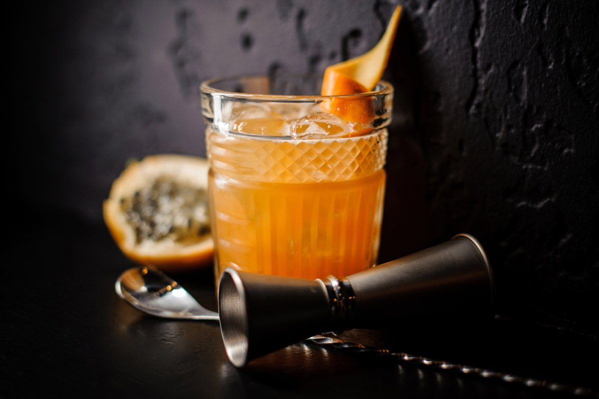 alcoholic cocktail of orange color in a stylish glass with ice and citrus