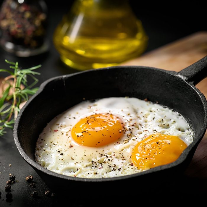 Fried eggs in a frying pan with cherry tomatoes and bread for breakfast on a black background