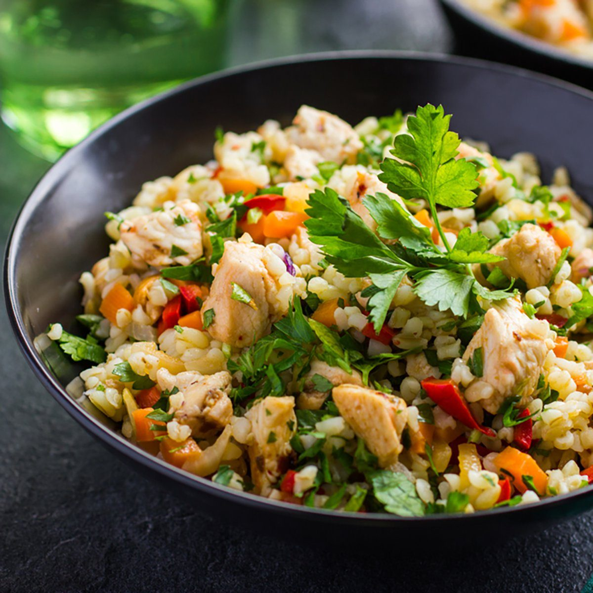 warm barley salad with chicken and vegetables, selective focus