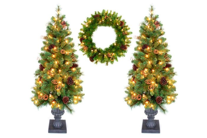 two lit holiday trees and a wreath on white background