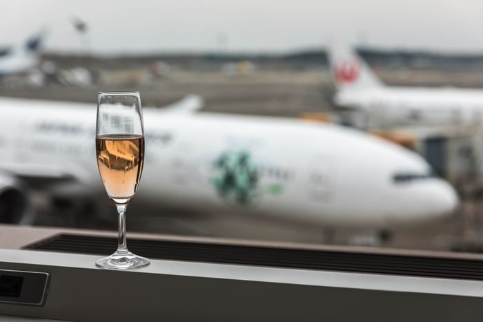 Narita airport, Tokyo, Japan, April 2018 - At airport lounge with a glass of champagne overlooking the runway.