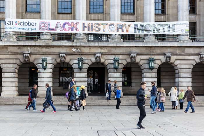 NOTTINGHAM, ENGLAND - OCTOBER 22: Various people walk past. Black History Month banner on front of Nottingham City Council House. In Nottingham, England. On 22nd October 2016.