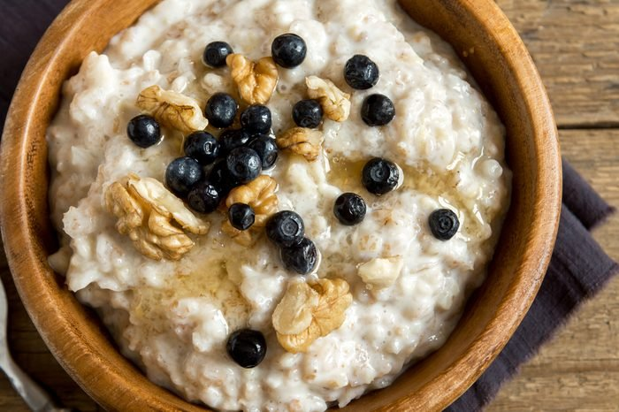Oatmeal porridge with walnuts, blueberries and honey in wooden bowl with copy space - healthy rustic breakfast