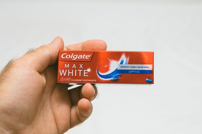 PARIS, FRANCE - JUL 27, 2018: Man holding Colgate small air security rules conformed travel toothpaste against white background