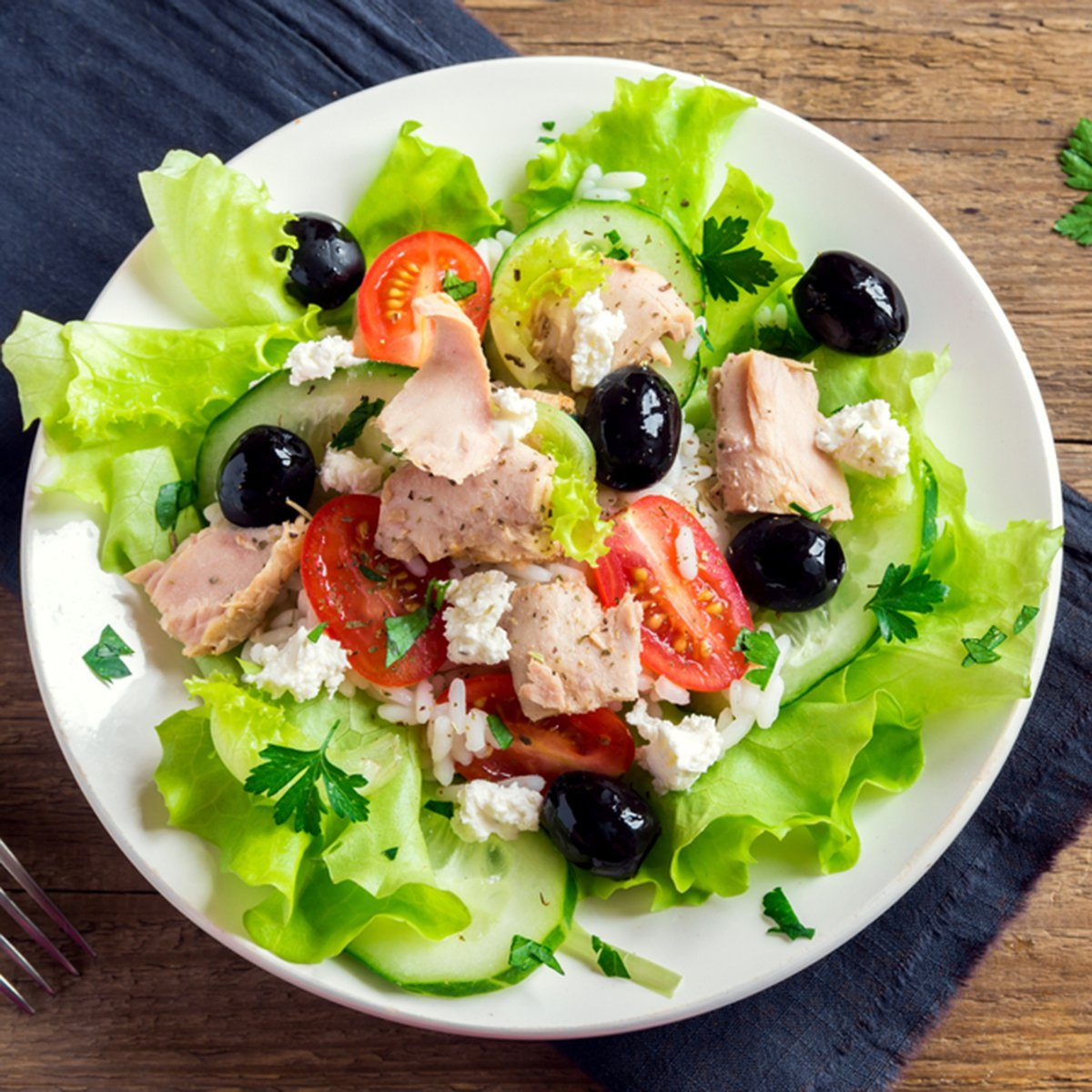 Tuna salad with tomatoes, black olives, rice, feta cheesse and greens on rustic wooden background with copy space