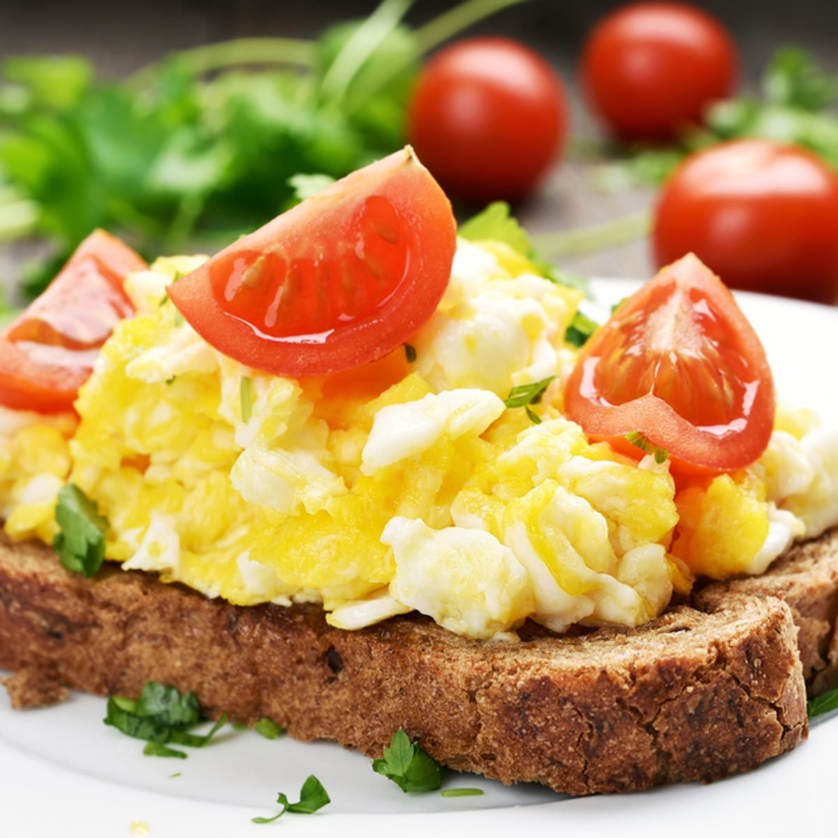 Breakfast scrambled eggs and tomato slices on bread