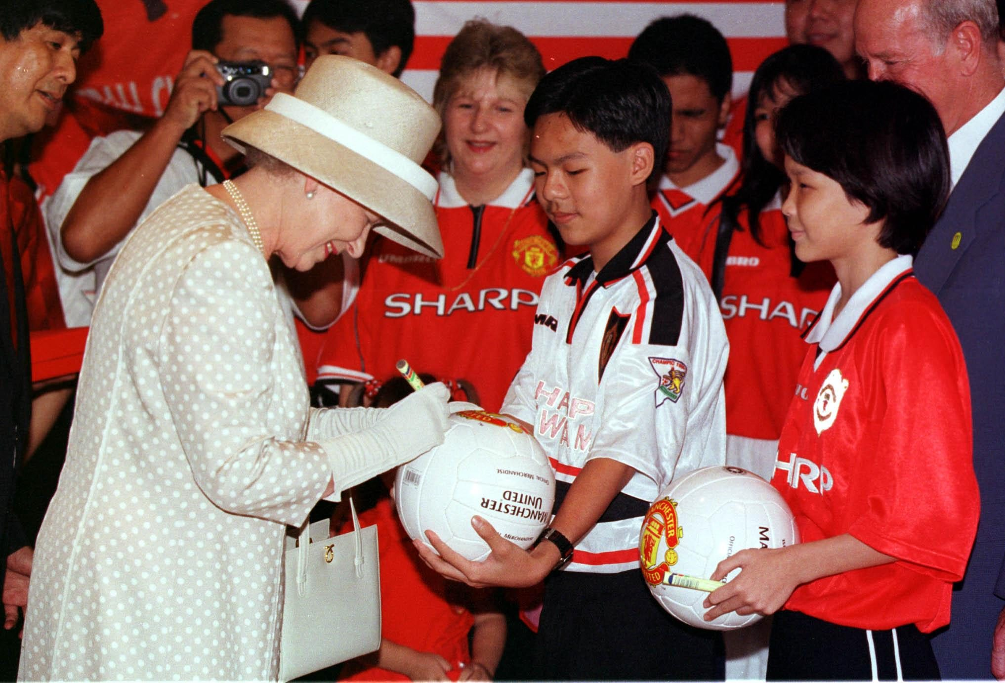 Queen Elizabeth Signs A Manchester United Football For The Mayalsian Branch Of The Manchester United Supporters Club In Kuala Lumpur Malaysia. 1998 . Rexmailpix.