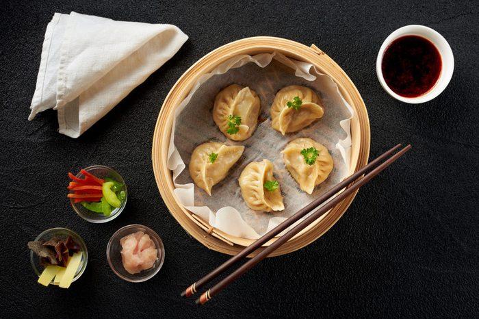 Dim sum dumplings in steamer and ingredients top view