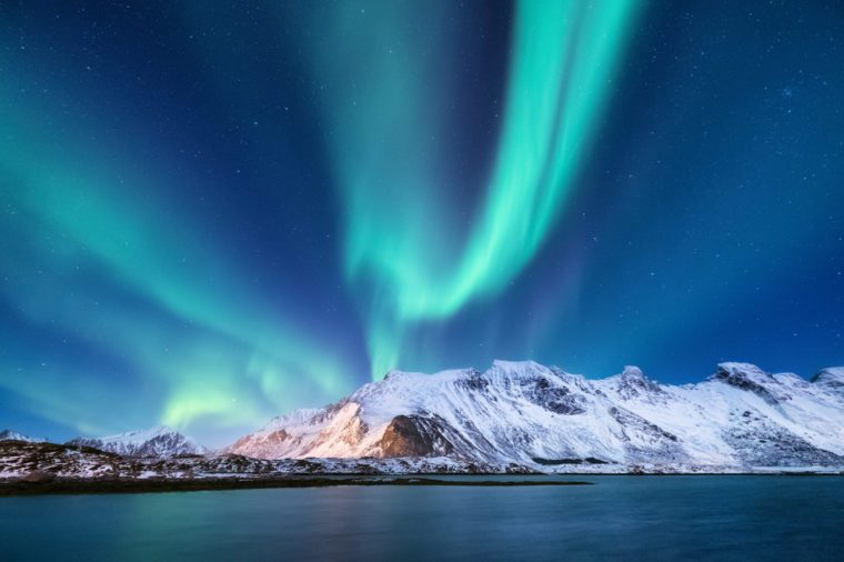 Aurora borealis on the Lofoten islands, Norway. Green northern lights above mountains. Night sky with polar lights. Night winter landscape with aurora and reflection on the water surface. Natural back