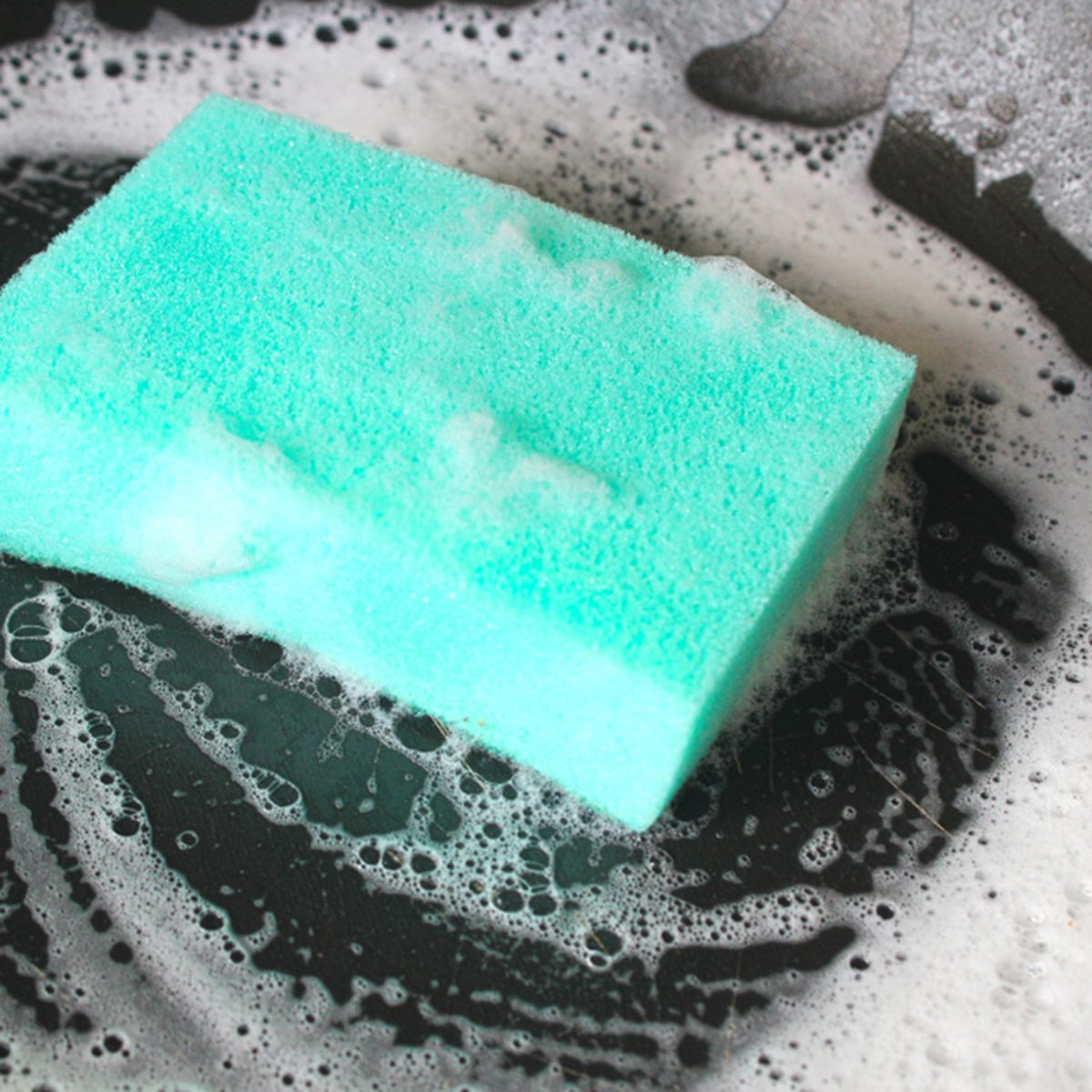 Cleaning Sponge with foam on a frying pan.
