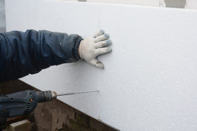 Contractor drilling wall for styrofoam insulation sheets holder.