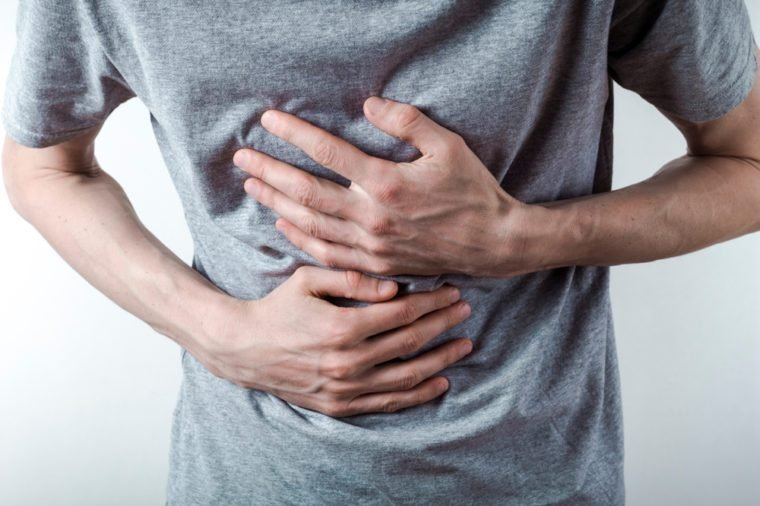 A man suffers from acid reflux in his chest. Heartburn.