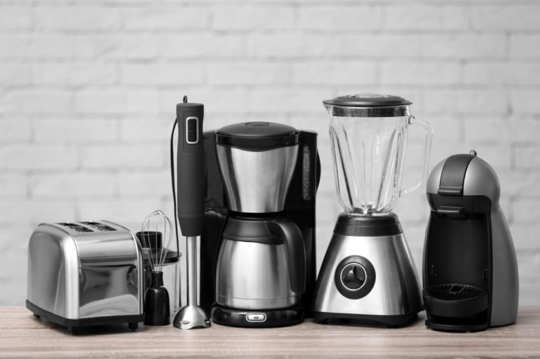 Kitchen appliances on table against brick wall background. Interior element