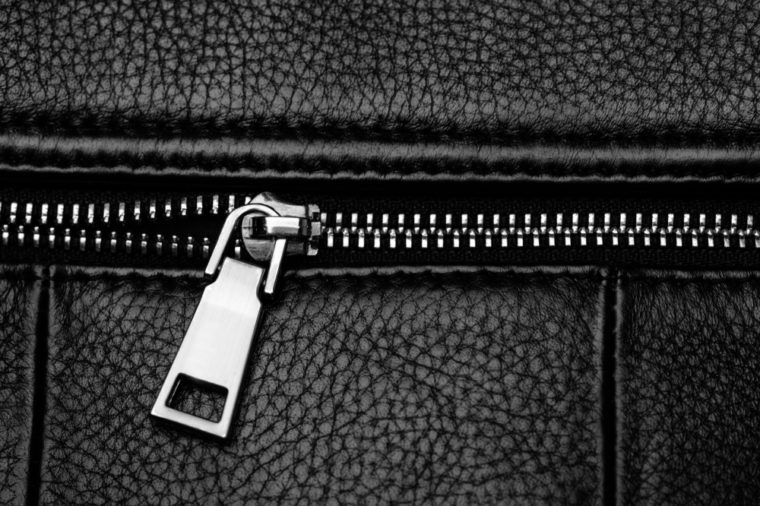 Black leather bag with silver zipper. Close-up of black leather.