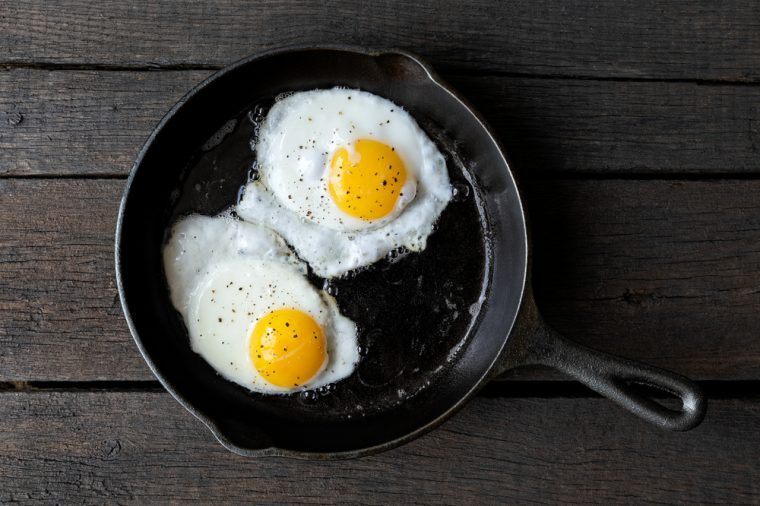 Two fried eggs in cast iron frying pan sprinkled with ground black pepper. Isolated on dark painted wood from above.