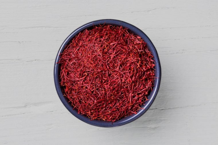Saffron threads in a round mug on white wooden background