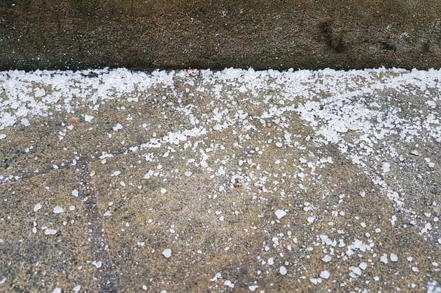 A lot of white salt is covered on the brown cement path to stop icy in the freezing night, feeling very cold. Concept salt, path and the safe in winter.