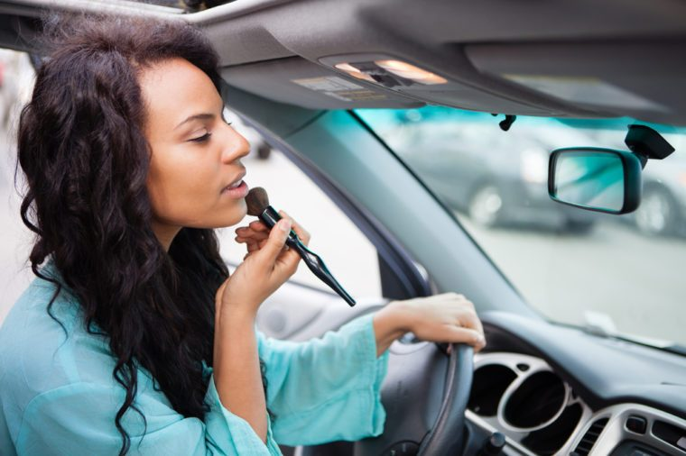 Attractive young woman touching up her make up in a Car looking in the rear view mirror