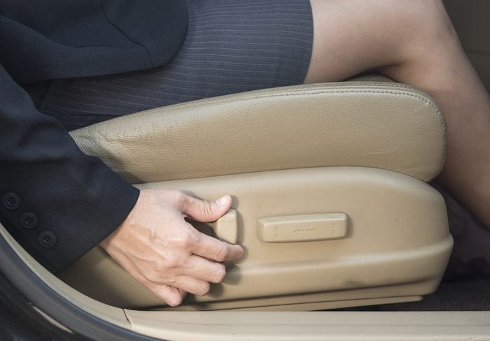Businesswoman adjusts power seats, seat in the car